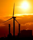 Electric power station and wind turbine at sunrise Stock Image