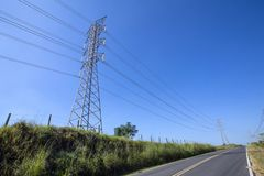 Electric power towers on the highway. Electric power transmission towers, on the side of the highway in perspective Stock Photos