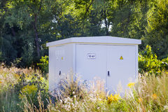 Electric power transformer in a meadow Royalty Free Stock Image