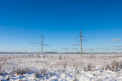 Electric power transmission in the field winter Royalty Free Stock Photo