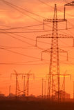 Electric power transmission lines at sunset Stock Images