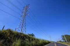 Electric power towers on the highway. Electric power transmission towers, on the side of the highway in perspective Royalty Free Stock Image