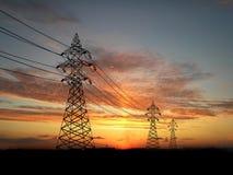 Electric powerlines. Over orange sky Stock Photos