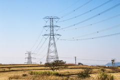 Electric Powerlines and Pylons on Winter Landscape. Overhead electric powerlines and pylons stretching across dry rural winter landscape in South Africa Royalty Free Stock Photography