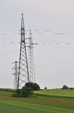 Electric pylon. High voltage electric pylon in green field Royalty Free Stock Images