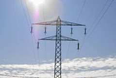 Electric Pylon over the clouds in the sun Stock Image