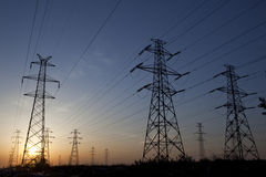 Electric pylons at dask. Electricity pylons and lines above a freeway at sunset Stock Photos