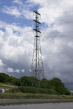 Electric Pylons. On Devon side of the River Tamar, with cloudy bright sky and muddy river bank royalty free stock photos