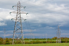 Electric pylons. Electricity pylons used to distribute national grid energy over land often contested for planning permission being unsightly and polluting the Stock Photos