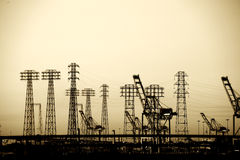 Electric Pylons in the Industrial Port. The industrial port of Los Angeles with cranes, electricity pylons and industrial buildings Stock Photos