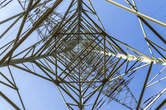 Electric pylons transporting electricity through high tension ca Stock Photos