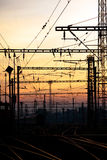 Electric railway. Trolley poles and towers at rail junction on sunset Stock Photos