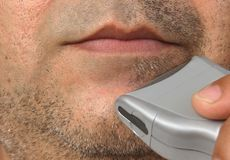 Electric razor and man's beard. Closeup of a man's shaving session Stock Images