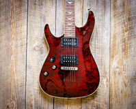 Electric red guitar body on wooden board background Stock Image