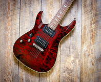 Electric red guitar body on wooden board background Royalty Free Stock Image