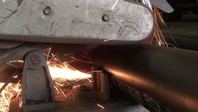 Electric saw cuts round pipe, close-up view from the side stock video footage