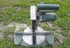 Electric saw on green lawn stock photos