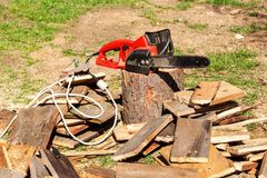 Electric saws and chainsaw. Electric saw chain on the background of sawn timber. The concept of processing wood to produce fuel. Stock Image