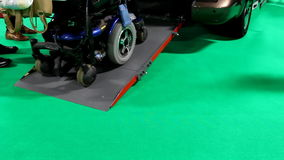 Electric scooter getting out of car. Electric scooter for disabled driving out of a car or van using ramp isolated on green background stock video