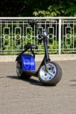 Electric scooter with wide wheels stands on the asphalt in the park. Scooter on an electric battery on the asphalt near an iron fence Stock Photo