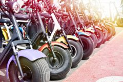Electric scooters for rent in parking. Electric scooters for rent in the parking lot in sunny weather royalty free stock image