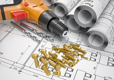 Electric screwdriver, fastening hardware, borers,. Electric screwdriver, fastening hardware, borers and scrolled drafts placed on  spread architectural drawing Royalty Free Stock Images