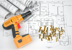 Electric screwdriver, fastening hardware, borers,. Electric screwdriver, fastening hardware, borers and scrolled drafts on spread architectural drawing Royalty Free Stock Photos
