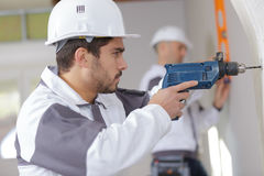Electric screwdriver in hand at construction site Stock Photo