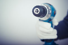 Electric screwdriver in hand at white desk background Royalty Free Stock Image