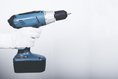 Electric screwdriver in hand at white desk background Stock Photos
