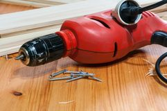 An electric screwdriver and some screws on a wooden table. A red electric screwdriver and some screws on a wooden table. Horizontal composition Royalty Free Stock Photos