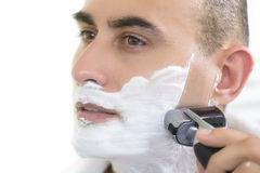 Electric Shaver. Young man shaving using electric shaver Stock Images