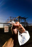 Electric Shock. Male Fist clenching an electric bill for $14,300 in front of an electrical power substation Royalty Free Stock Photo