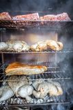 Electric smoker loaded with variety of meat royalty free stock images