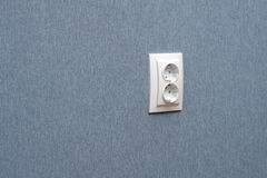 Electric socket. The white electric socket on a blue wall Royalty Free Stock Image