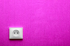 The electric socket in a pink wall Royalty Free Stock Image