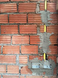 electric sockets installation in brick walls at house constructi Stock Image
