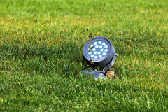 Electric spotlight in green grass stock photography