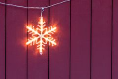 Electric star home Christmas decoration. Electric star hanging outside wooden home during Christmas in winter stock image