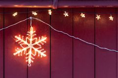 Electric star home Christmas decoration. Electric star hanging outside wooden home during Christmas in winter royalty free stock photo