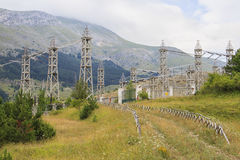 Electric station in the mountains. An electric implant between mountains with many high-voltage poles and cables Royalty Free Stock Photos
