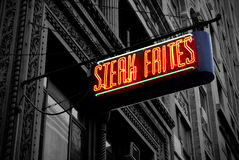 Electric Steak Frites. A neon sign shines in colour on a rich black-and-white architectural backdrop Royalty Free Stock Image