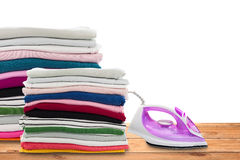 Electric steam iron and Pile of colorful clothes on wooden floor. Royalty Free Stock Photo