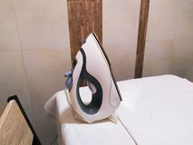 Electric steam iron on the table stock photo