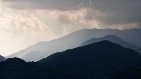 Electric storm over the wind farm, turbines. Lunigiana, Italy. Dark sky and getting darker. Lightning added in post production for metaphor: storm over turbines Stock Image