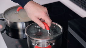 On electric stove pan frying-pan, man prepares dinner, salts water stock video