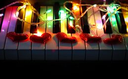 Electric string light and five red glitter hearts on piano keyboard
