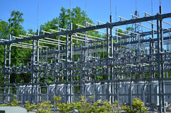Electric Substation Closeup. Large electrical substation fenced in with large Pine Trees in the background and bright blue sky Stock Images