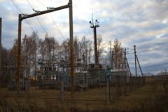 Power transformer in a distribution substation separated from another one by a wall. Electric substation in Russia field stock photo