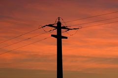 Electric sunset. Electrical pillar silhouette in the sunset Royalty Free Stock Image